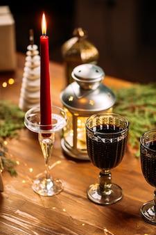 Świątecznie udekorowany stół z kubkami wina błyszczącego i świecami