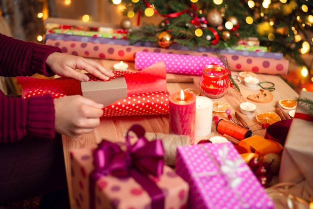Świątecznie udekorowany stół z wieloma zapakowanymi prezentami i dekoracjami