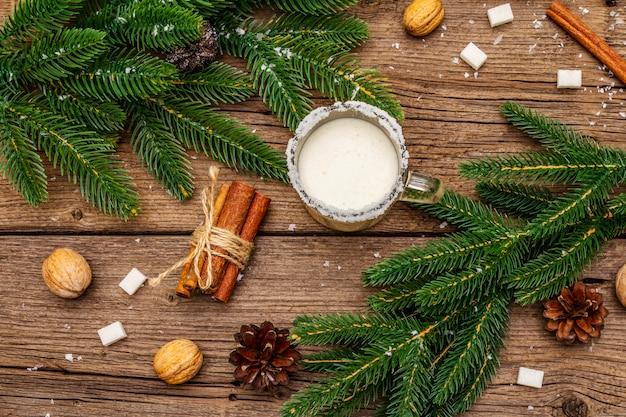 Świąteczny ajerkoniak likier lub koktajl cola de mono. klasyczny zimowy napój w szklanym kubku, ozdoby świąteczne. zimozielone gałęzie, cynamon, orzechy włoskie, cukier.