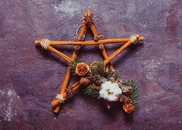 Świąteczny aromatyczny wystrój, laski cynamonu związane w pięcioramienną gwiazdę ze sznurkiem, żołędziami i kwiatem bawełny
