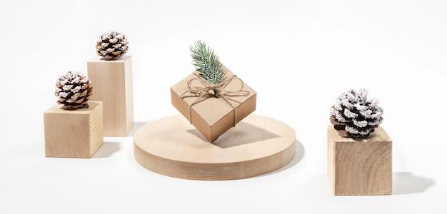 Świąteczny baner świąteczny z szyszkami i zrównoważonym pudełkiem na prezent diy na drewnianych podium na białym tle. transparent.