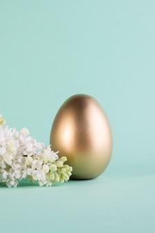 Świąteczny baner z dużą złotą pisanką, kwiat bzu na jasnoniebieskim tle.