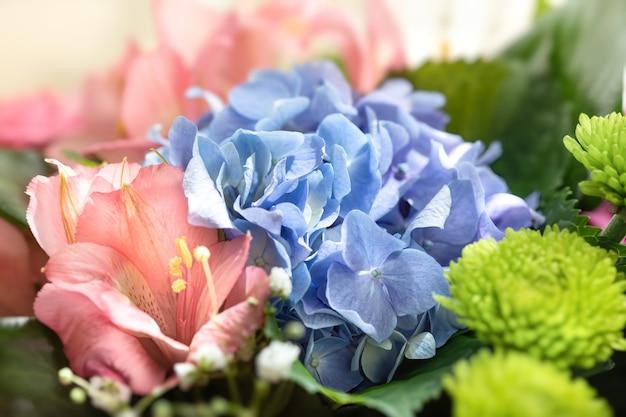 Świąteczny bukiet różnorodnych kwiatów, w tym niebieskiej hortensji i różowej alstremerii