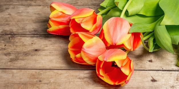 Świąteczny bukiet świeżych tulipanów na zabytkowym drewnianym stole