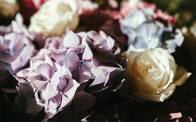 Świąteczny bukiet z bukietu róż i hortensji w promieniach słońca. kwiat w tle