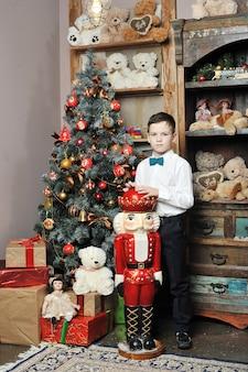 Świąteczny chłopak i dziadek do orzechów wokół choinki z prezentami