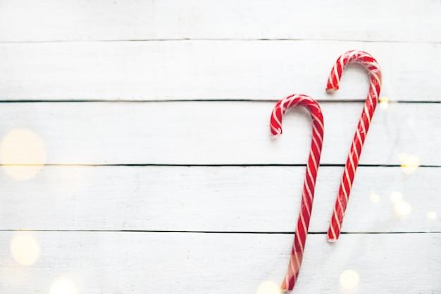 Świąteczny cukierek z girlandą na białym drewnianym tle