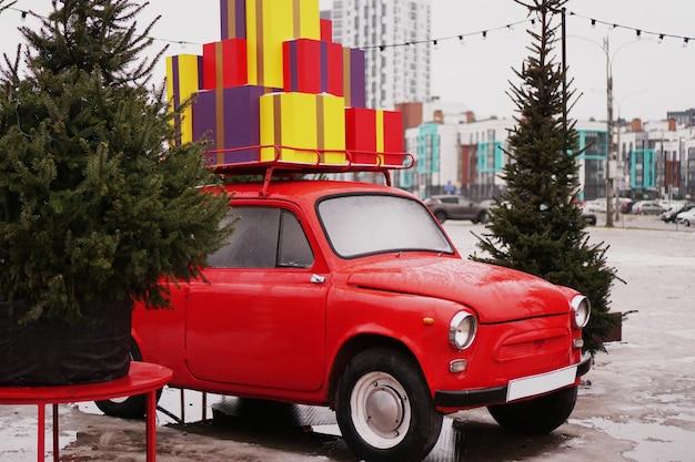 Świąteczny czerwony samochód retro z pudełkami na prezenty, choinka na zewnątrz