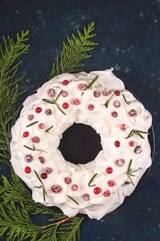 Świąteczny deser bezy pavlova z bitą śmietaną przyozdobioną żurawiną i rozmarynem.