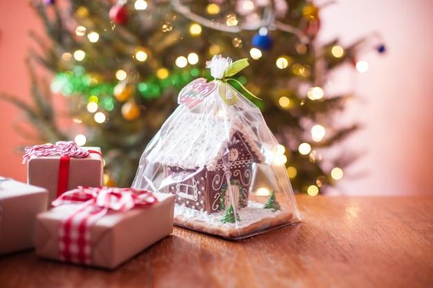 Świąteczny domek z piernika i pudełka z prezentami na stole