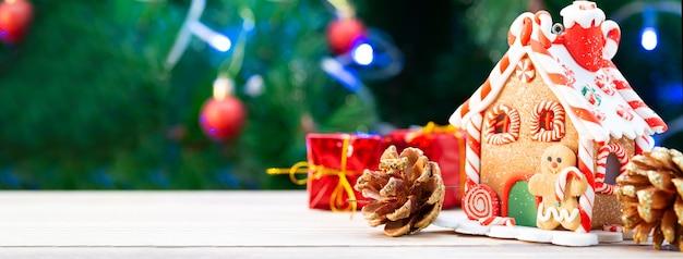Świąteczny domek z piernikowych ciasteczek ozdobiony świąteczną atmosferą z choinką w tle. domek z piernika na tle choinki, miejsce na tekst