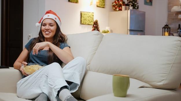 Świąteczny dorosły śmiejący się i oglądający film w telewizji
