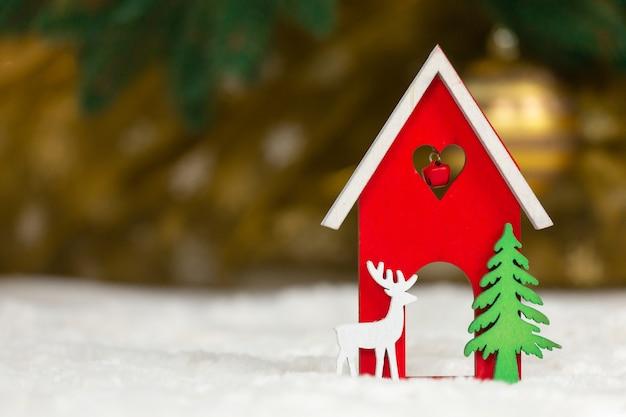 Świąteczny drewniany domek, jeleń i drzewo na białym kocu imitującym śnieg.