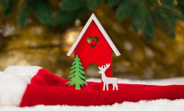 Świąteczny drewniany domek z zabawkami, jeleń i drzewo na czapce mikołaja i białym kocu imitującym śnieg
