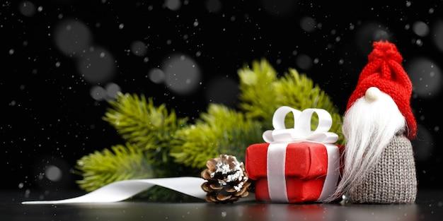 Świąteczny gnom z czerwonym pudełkiem i dekoracjami świątecznymi