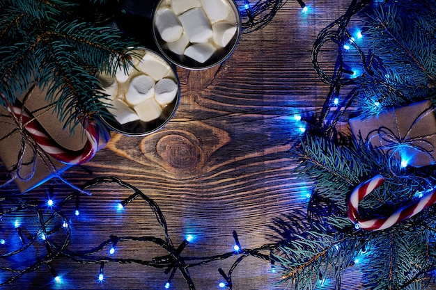 Świąteczny gorący napój. kakao z pianką, pudełkiem prezentowym, lampkami choinkowymi, girlandą i świerkowymi gałązkami na drewnianym tle. widok z góry. skopiuj miejsce. leżał płasko. martwa natura. makieta