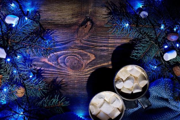 Świąteczny gorący napój kakaowy z girlandą prawoślazu i gałązkami świerkowymi na drewnianym tle widok z góry