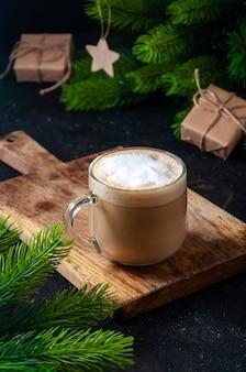 Świąteczny gorący napój. kawa kakaowa lub czekolada w okularach na ciemnym stole z pudełkiem na prezent i gałęziami jodły.