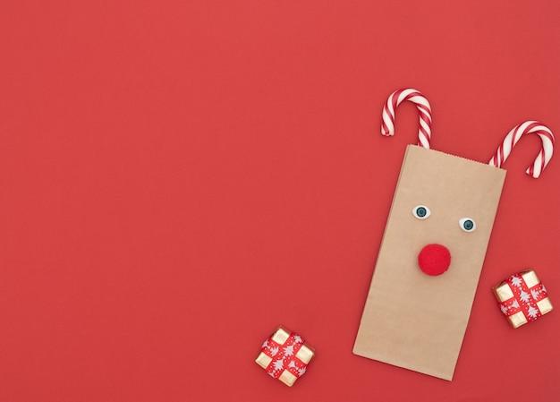 Świąteczny jeleń wykonany z rzemieślniczej torby na zakupy i dwóch lasek bożonarodzeniowych z pudełkami na czerwonym tle. kartkę z życzeniami nowego roku. koncepcja bożego narodzenia i nowego roku. płaski styl świecki z miejscem na kopię.