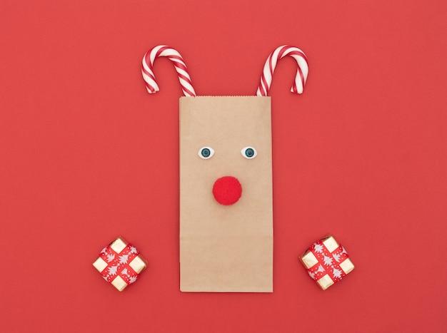 Świąteczny jeleń wykonany z rzemieślniczej torby na zakupy i dwóch świątecznych lasek z pudełkami na prezenty