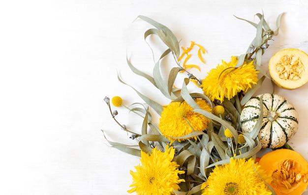 Świąteczny jesienny wystrój z dyni i kwiatów na białym tle, miejsce. koncepcja święta dziękczynienia lub halloween.