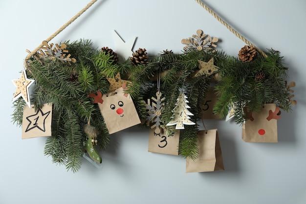 Świąteczny kalendarz adwentowy z gałązkami świerkowymi wiszącymi na ścianie.