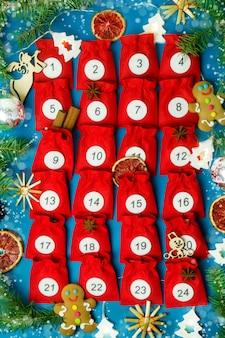 Świąteczny kalendarz adwentowyczerwone torebki z numerami na niebieskim tle