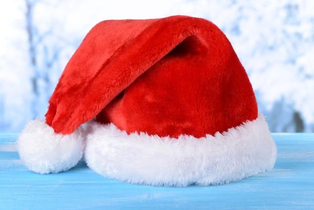 Świąteczny kapelusz na stole na jasnym tle