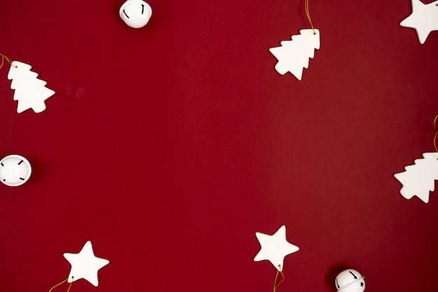 Świąteczny karciany tło z ceramicznymi białymi bożenarodzeniowymi zabawkami na czerwonym tle z przestrzenią.