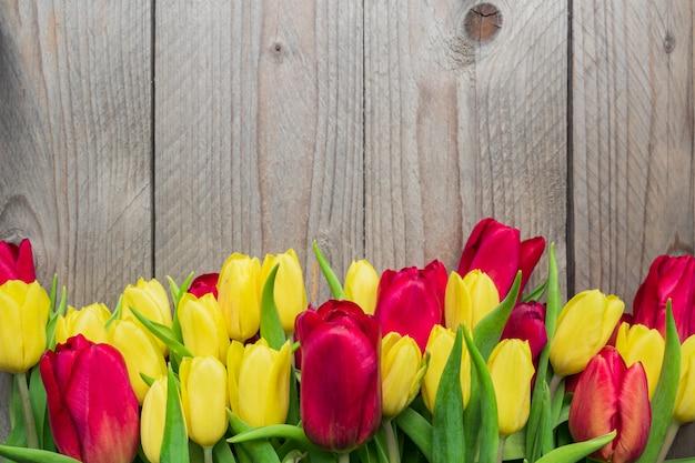 Świąteczny kartkę z życzeniami z żółtymi i czerwonymi tulipanami na drewnianym tle. skopiuj miejsce na tekst