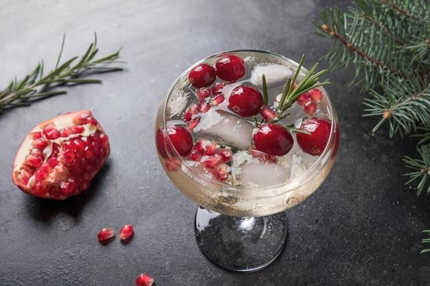 Świąteczny koktajl z granatów z rozmarynem, szampanem, sodą klubową na czarnym tle. ścieśniać.