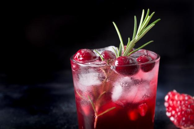 Świąteczny koktajl z granatów z rozmarynem, winem musującym, soda klubowa na czarnym tle. ścieśniać.