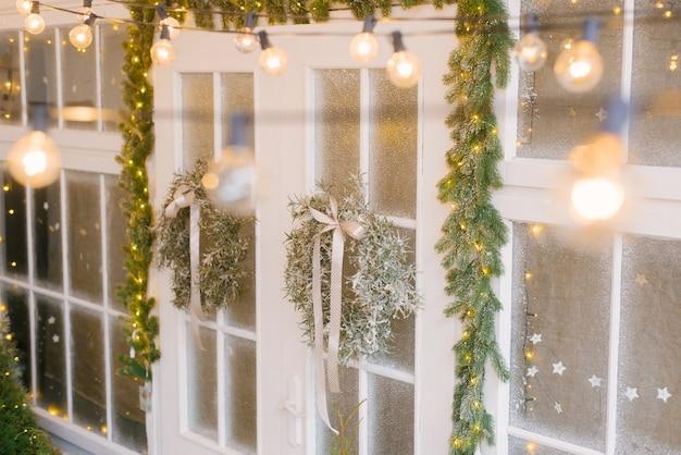 Świąteczny komfort. wieńce choinkowe na białych drzwiach otoczone licznymi światłami