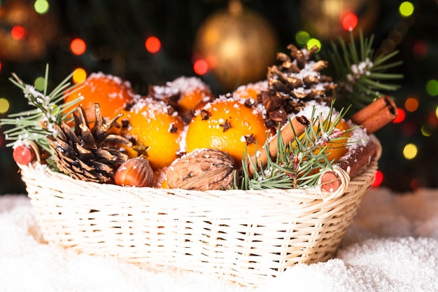 Świąteczny kosz - jodła, mandarynki i przyprawy pod śniegiem