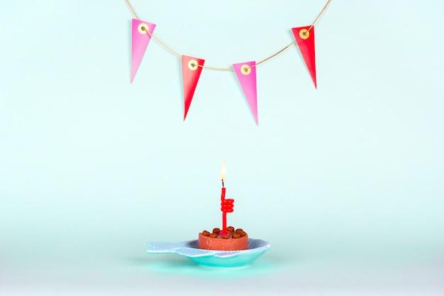 Świąteczny kota tort z płonącą świeczką i dekoracją na ścianie na lekkim tle