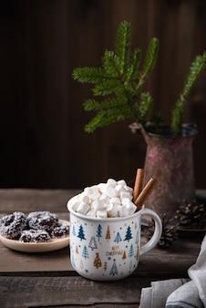 Świąteczny kubek kakao i prawoślazu z cynamonem na starym brązowym drewnianym stole z ciasteczkami i jodłą. noworoczny nastrój. widok z przodu i miejsce na kopię