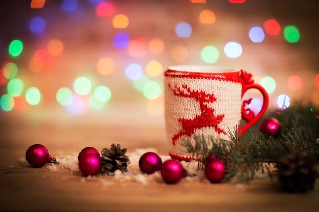 Świąteczny kubek z dekoracjami i słodyczami na podłoże drewniane