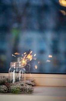Świąteczny lub nowy rok party ognie w słoiku przed oknem na ciemnym tle świąteczny wystrój