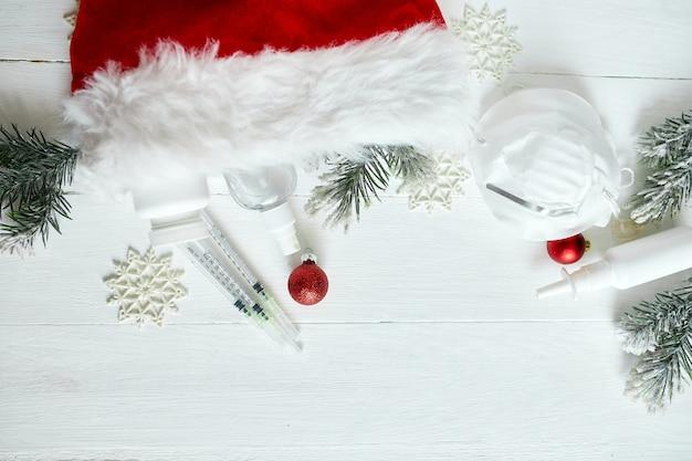 Świąteczny medyczny koronawirus płaski leżał, ochronna maska na twarz, pigułki, środki antyseptyczne, dekoracja na białym tle, motyw noworoczny