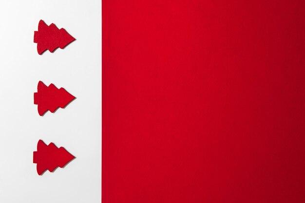 Świąteczny minimalistyczny sztandar z jodłami na białym tle i czerwoną wolną przestrzeń