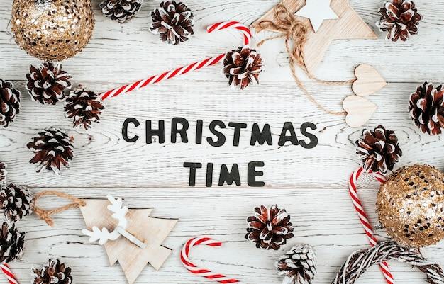 Świąteczny napis wykonany z czarnych drewnianych liter otoczonych szyszkami