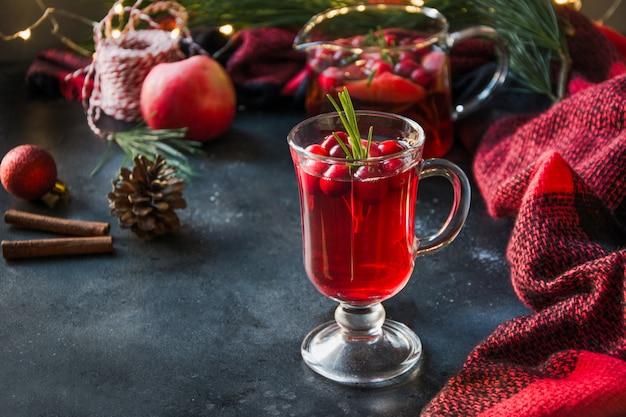 Świąteczny napój żurawinowy i jabłkowy ozdabia rozmaryn i jodłę na czarno.
