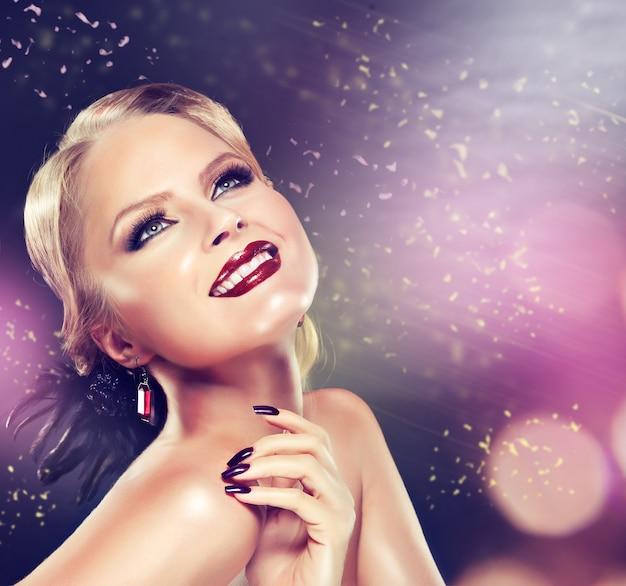 Świąteczny nastrój i szeroki uśmiech na twarzy blondynki z makijażem w stylu czarnych zadymionych oczu. elegancka fryzura, jasny makijaż i czarny manicure.