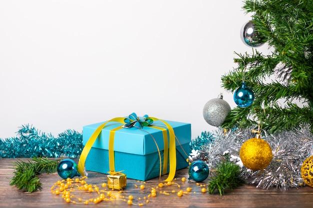 Świąteczny nastrój. prezent z niebieskimi kulkami owiniętymi w opakowania i małymi złotymi prezentami umieszczonymi na drewnianym stole i na białym. magia.