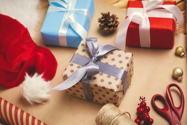 Świąteczny nastrój świąteczny. płaskie układanie dekoracji, wstążki, papier prezentowy, zapakowany prezent na drewnianym