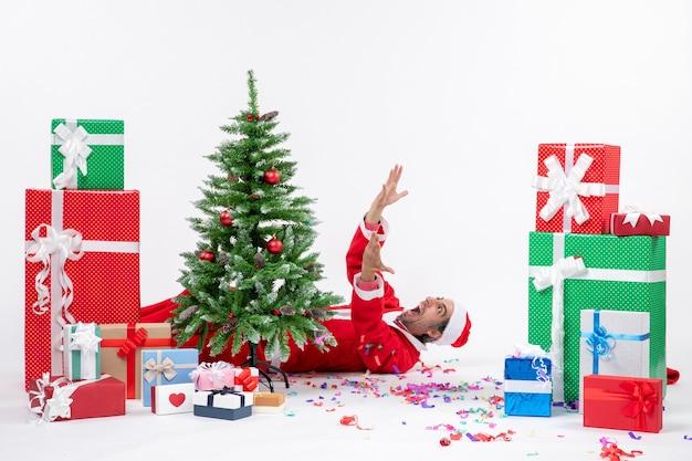Świąteczny nastrój świąteczny z młodym emocjonalnym mikołajem leżącym za choinką w pobliżu prezentów na białym tle