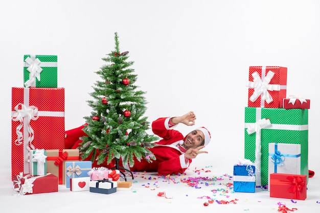 Świąteczny nastrój świąteczny z młodym mikołajem leżącym za choinką i pokazującym dwa obok prezentów na białym tle
