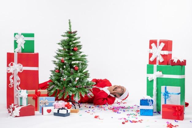 Świąteczny nastrój świąteczny z młodym zaskoczonym mikołajem leżącym za choinką w pobliżu prezentów na białym tle