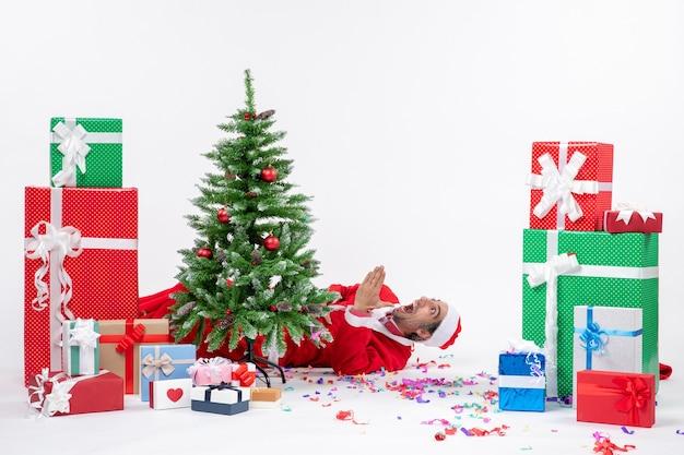 Świąteczny nastrój świąteczny z młodym zszokowanym mikołajem leżącym za choinką w pobliżu prezentów na białym tle
