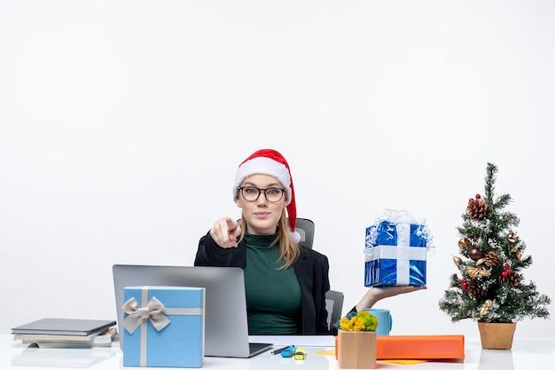 Świąteczny nastrój z ciekawą pozytywną młodą kobietą w czapce świętego mikołaja i noszących okulary siedzącą przy stole pokazującym prezent wskazujący kogoś na białym tle